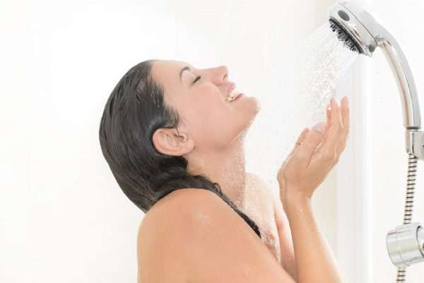 Woman taking a shower enjoying water splashing on her
