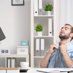 Should I Repair or Replace My Air Conditioning Unit?-Young man feeling hot in office
