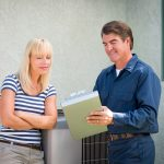 Air Conditioner Repairman talking to woman