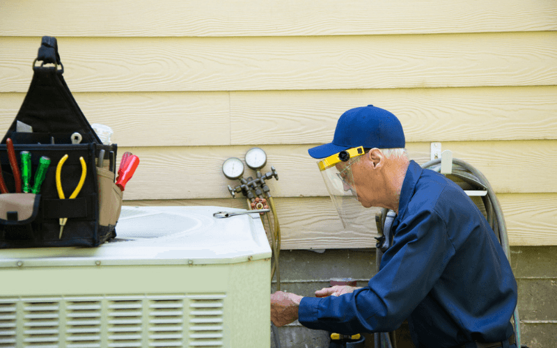 repair man working on air conditioner