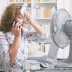 A woman on the phone with a towel on her head in front of a fan to decide if she should repair or replace her air conditioning